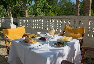 Dekket bord med hvit duk og gule stoler langs hvitt gjerde i solveggen, forskjellige albanske matretter servert på bordeet med vinkaraffel