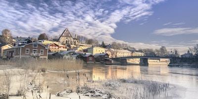 Vinter i Porvoo med hus og kirken i bakgrunnen, vann i forgrunnen