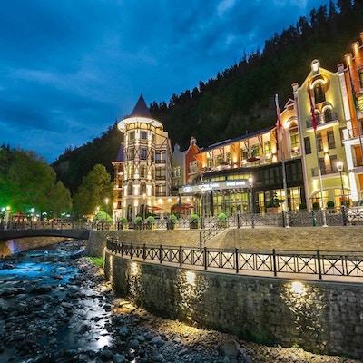 Kveldsbilde med hotell Crowne Plaza som er opplyst og ligger ved vannet med skogen i bakgrunnen