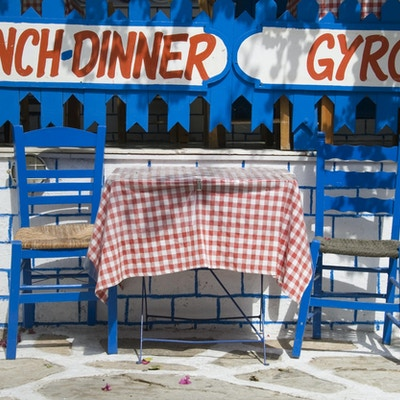 To blå stoler og et bord med rutete duk foran et skilt med lunch, dinner og gyros på vinduet