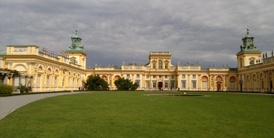Et stort slott bygget i halvsirkel med gul fasade og stor park tilknyttet
