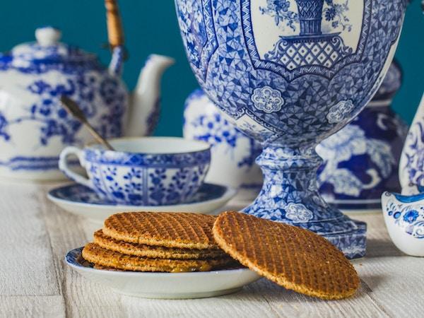 Tradisjonell nederlandsk stroopwafel med sirup, informasjonskapsel og te, Delfts blå dekorativ servise satt på bordet, nærbilde, makrofoto