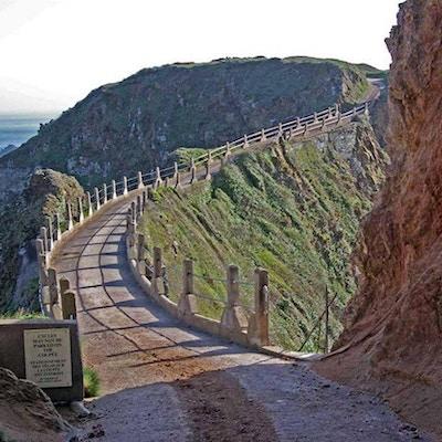 En liten grusvei med rekkverk slynger seg gjennom fjell og hei