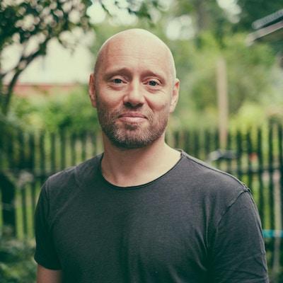 Portrettbilde av Aksel Hennie i grå t-skjorte