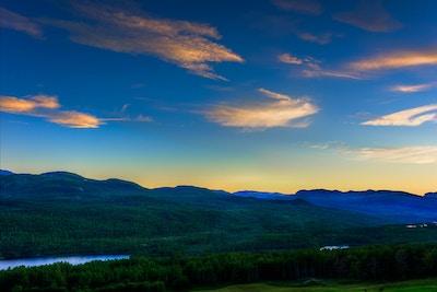 Landskapsbilde med blå himmel med oransje skyer i solnedgangen over de grønne trærne i Espedalen, med utsikt mot vann og fjell
