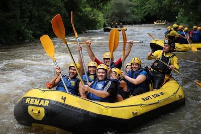 Raftingflåte med glade deltakerne med gule hjelmer