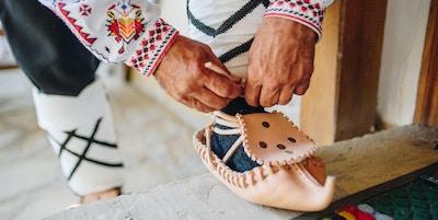 Mann som klær på seg tradisjonelle bulgarske lærsko - Tsarvuli