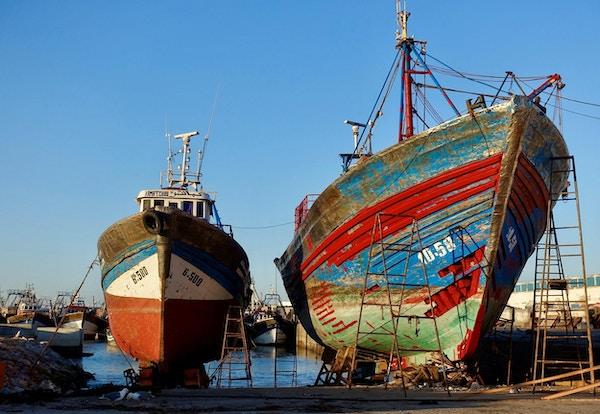 to fiskebåter i land ved en havn under reparasjon