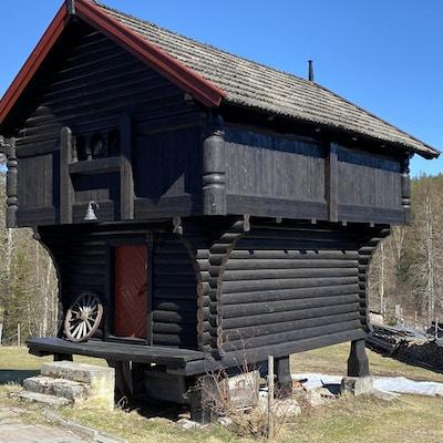 Et brunbeiset stabbur med rød dør og møner og et gammelt kjerrehjul ved døra