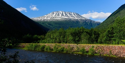 Fjellet Gaustatoppen dekket av snø på topp sett på avstand med vannet og skog foran