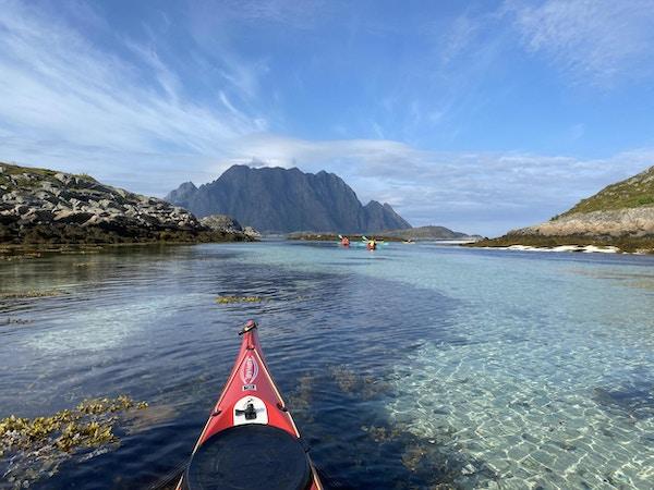 Kajakkpadling på krystallklart hav med sandbunn og tang med fjell og blå himmel i bakgrunnen