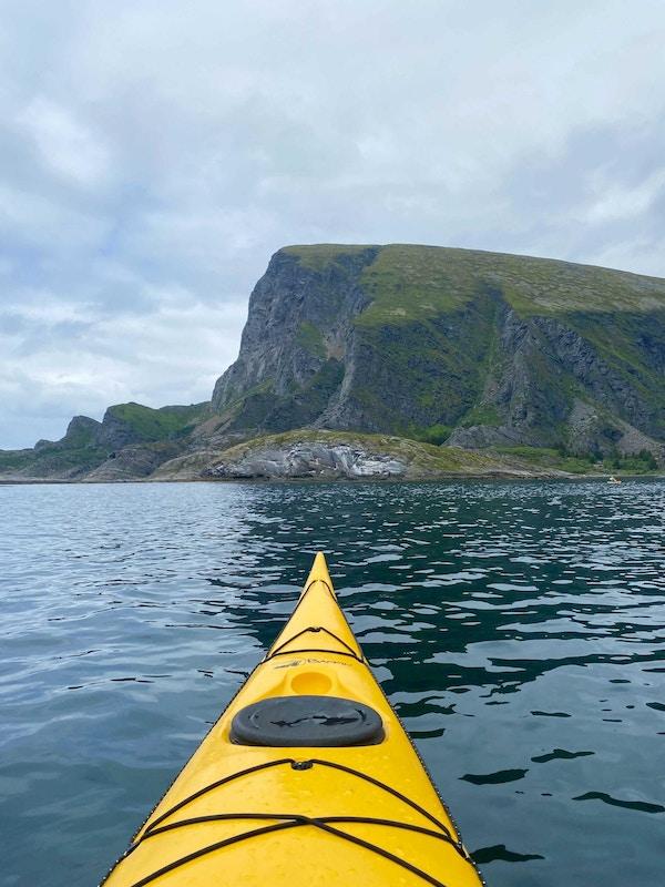 Fronten på en gul kajakk i havet med Lovundfjellet i bakgrunnen og overskyet himmel