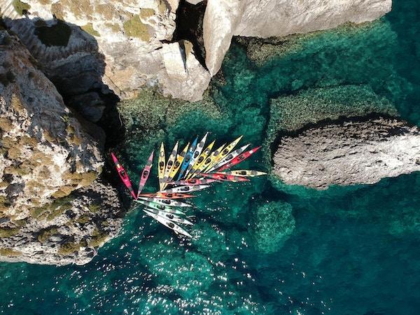 Fargerike kajakker i en trang bukt i havet utenfor Kefalonia
