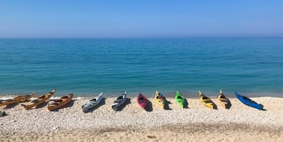 Elleve kajakker i forskjellig farge ligger på rad og rekke på stranden foran det turkise havet