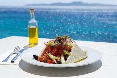 Gresk salat og olivenolje på solfylt havoppsett