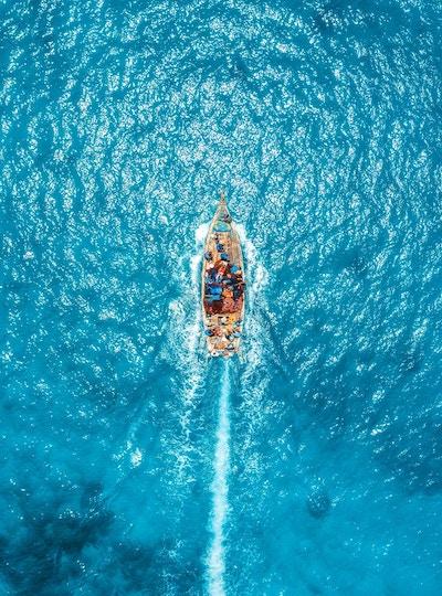 Flyfoto av fiskebåten i gjennomsiktig blått vann på solrik dag om sommeren. Topp utsikt fra drone av flytende båt i det indiske hav i Zanzibar, Africa. Landskap med yacht i klart hav. Seascape