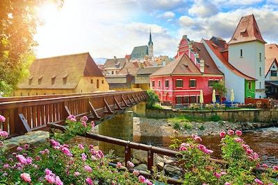 Tsjekkiske Krumlov, (Cesky Krumlov), Tsjekkia. Trebro over elven Vltava. Vintage pittoresk gammel by med fargerike hus og kirke kapell. Rose blomster på banken. Solrik sommerdag.