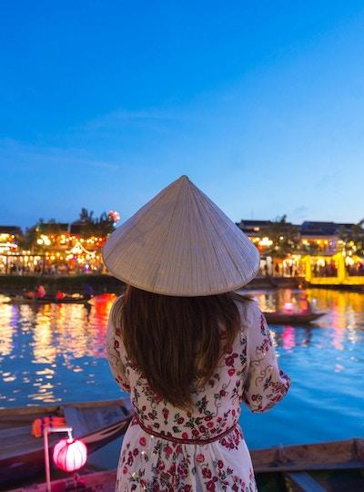 Kvinneturist er på sightseeing ved elven Thu Bon og bruker Non La (vietnamesisk hatt) i Hoi An, Vietnam.