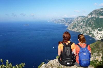 to damer sitter og ser ut mot havet