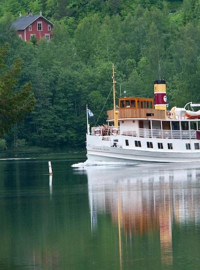 Båt som seiler langs kanalen med trær rundt