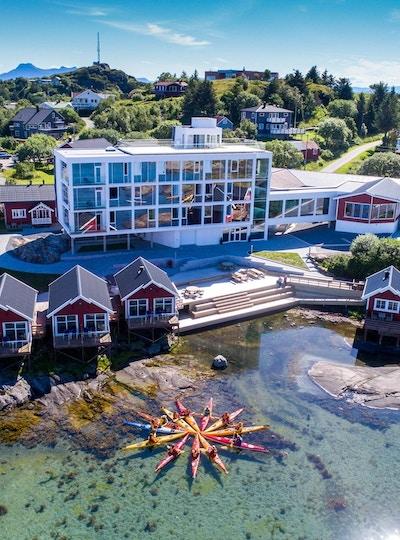 Bilde tatt ovenfra av mange kajakker som danner stjerneform med røde hus og Lovund Hotell i bakgrunnen