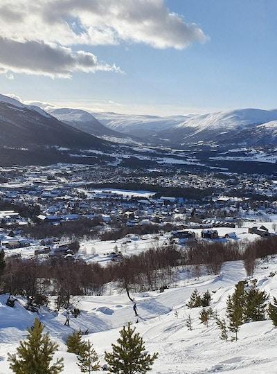 Utsikt over bygda Oppdal med fjellene rundt om vinteren