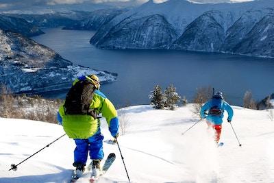To skikjørere på vei nedover fjellene i Luster
