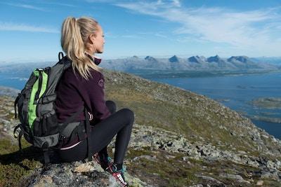 Jente på toppen av et fjell med ryggsekk ser utover havet