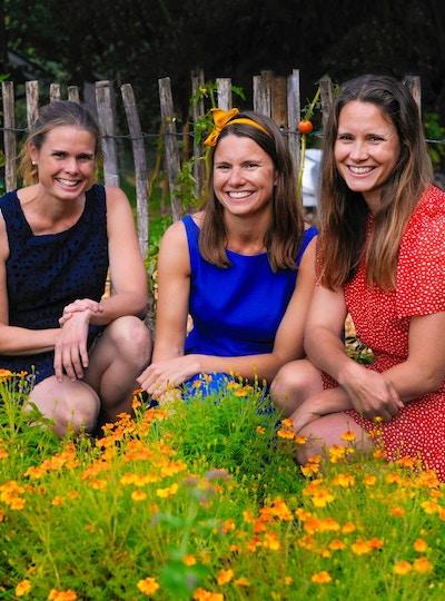 Tre jenter i fargerike sommerkjoler sitter i en blomstereng og ønsker velkommen